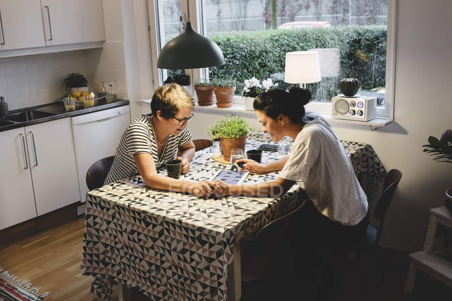 Lesbian couple using digital tablet while holding hands at dining table — Stock Photo