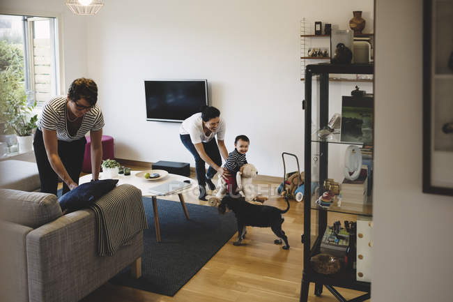 Mother and baby girl playing while woman working at home — Stock Photo