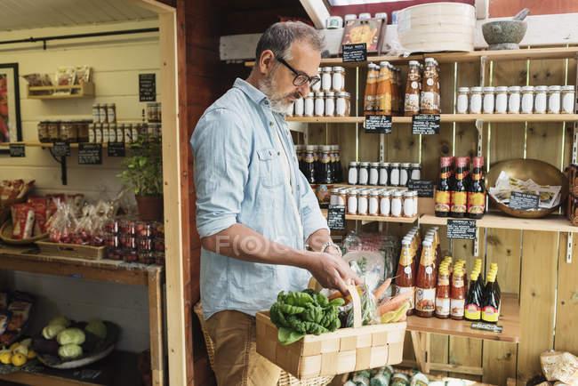 Uomo maturo che trasporta cestino durante lo shopping in negozio di alimentari — Foto stock