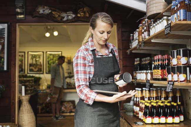 Impiegata donna che esamina il cibo in scatola con tablet digitale al supermercato — Foto stock