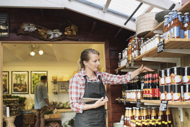 Female sales clerk with tablet arranging bottles on shelf at store — Stock Photo