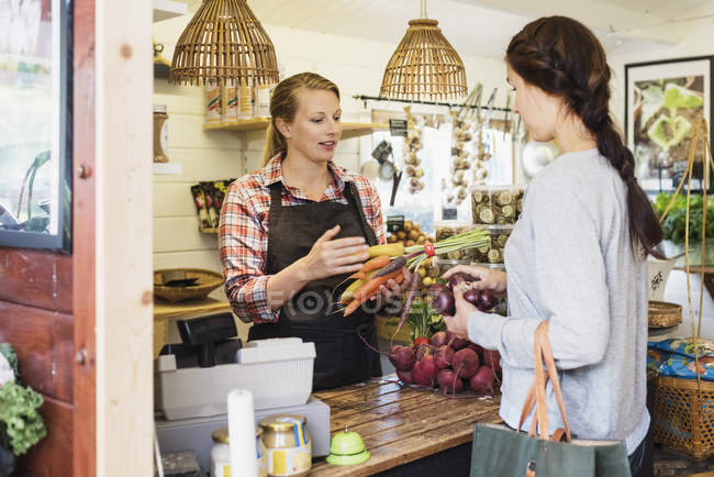 Female customer talking with cashier at health food store — Stock Photo