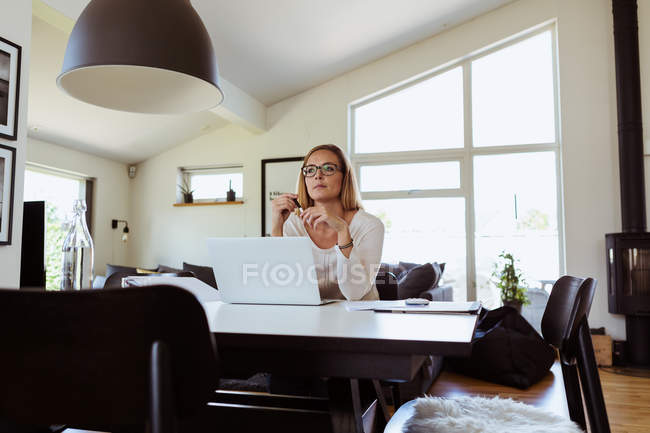 Thoughtful woman using laptop while sitting at table in living room — Stock Photo