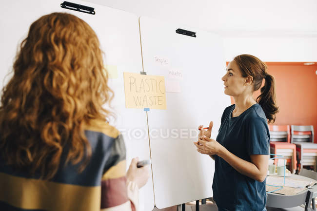 Confident female colleagues discussing plastic management project over whiteboard at creative office — Stock Photo