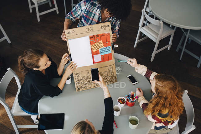 High angle view of manager photographing strategy on placard with technicians at creative office — Foto stock