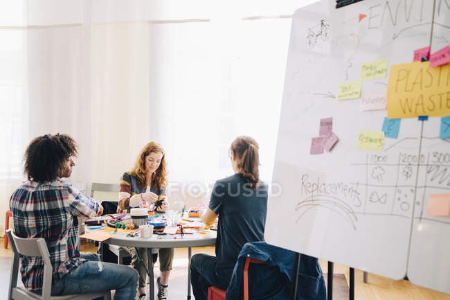 Multi-ethnic business colleagues working at table by whiteboard in creative office — Stockfoto