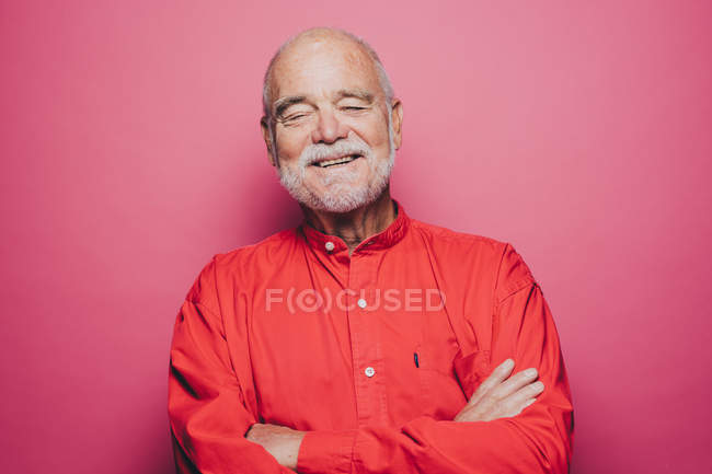 Smiling senior man with eyes closed against pink background — Stock Photo