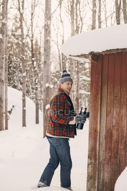 Smiling man holding drink container while walking by log cabin on snowy landscape — Stock Photo