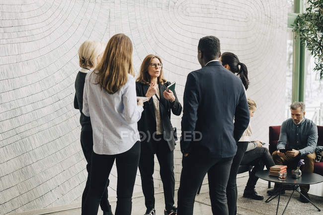 Mature businesswomen discussing with coworkers in meeting at office — Foto stock