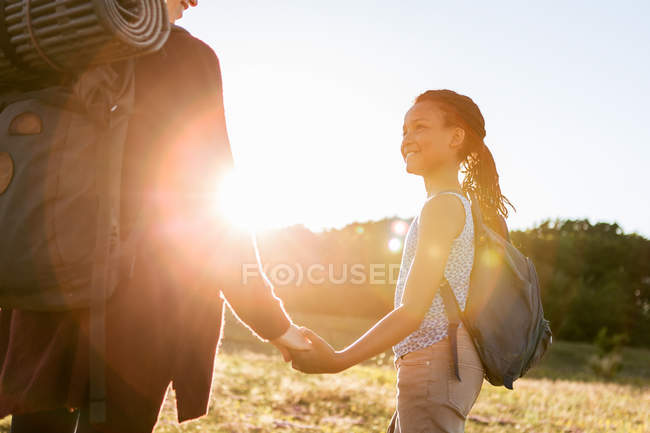 Lächelndes Mädchen hält Händchen mit Mutter beim Wandern im Park gegen den Himmel während des Sonnenuntergangs — Stockfoto