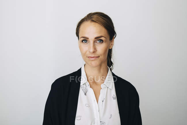 Portrait of confident mid adult businesswoman standing against white wall at creative office — стоковое фото