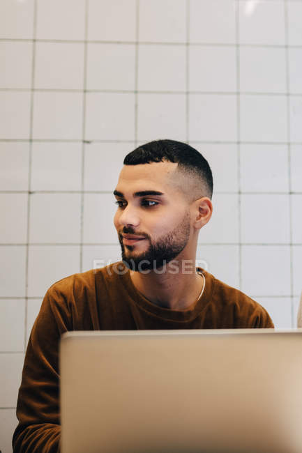 Young hacker looking away while sitting with laptop against wall at creative office — Stock Photo