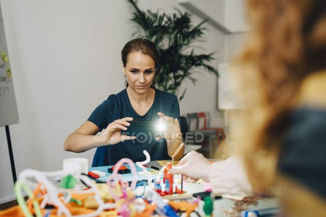 Selbstbewusste Geschäftsfrau fotografiert Schreibwaren auf Tisch im Kreativbüro — Stockfoto