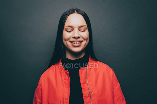 Young woman with eyes closed over gray background — Stock Photo
