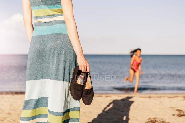 Mittelteil der Frau mit Schuhen, während Tochter bei sonnigem Wetter am Strand läuft — Stockfoto