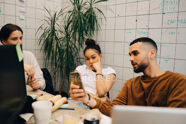 Young male hacker sharing smart phone with female colleagues while sitting at creative office — Stock Photo