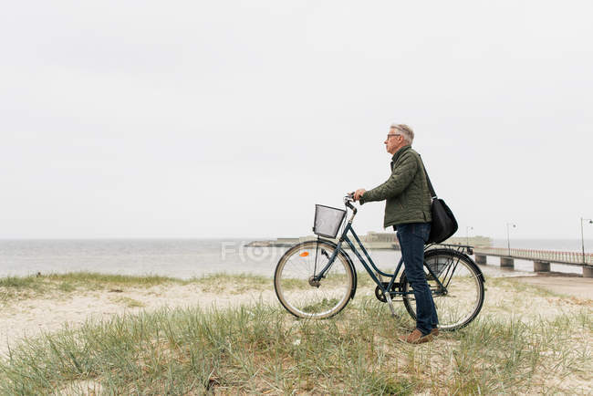Full length side view of senior male commuter standing with bicycle at beach against clear sky — Stock Photo