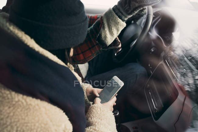 High angle view of woman using smart phone while sitting with friend in car — Stock Photo