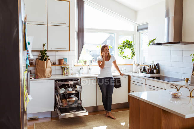 Smiling woman talking on mobile phone while standing in kitchen — Stock Photo