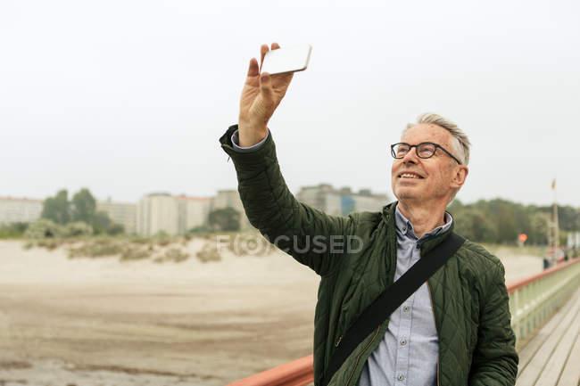 Hombre mayor sonriente tomando selfie mientras está de pie en el muelle en la playa contra el cielo despejado - foto de stock