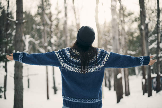 Rear view of woman standing with arms outstretched on snowy field during winter — Stock Photo