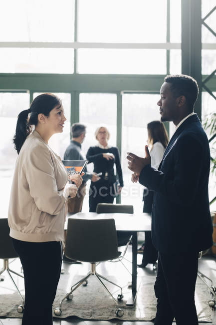 Businessman sharing ideas with female coworker in meeting at office — Stock Photo