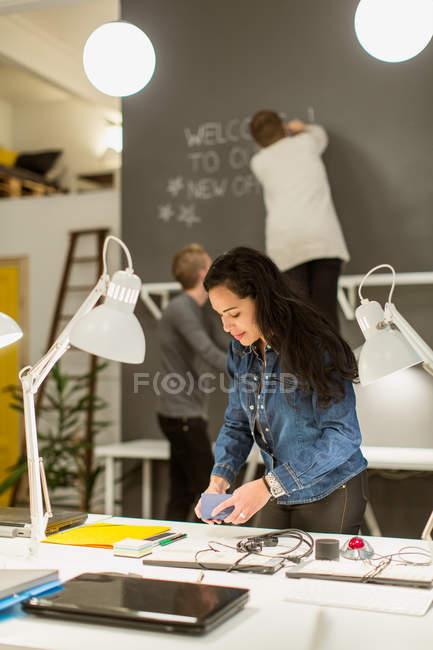 Mujeres jóvenes empresarias adultas que organizan un escritorio contra colegas que trabajan en una oficina creativa - foto de stock