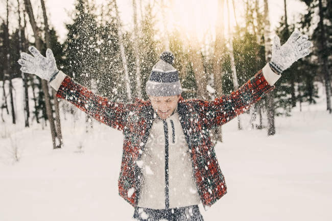 Happy mid adult man playing with snow on snow covered field — Stock Photo