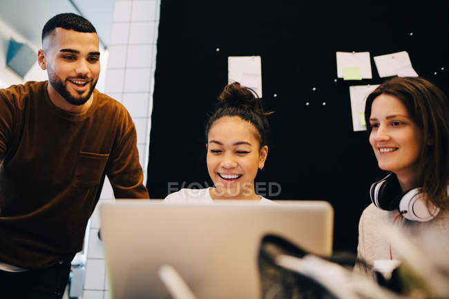 Smiling young businesswoman discussing with multi-ethnic colleagues over laptop against bulletin board at office — Stock Photo