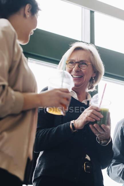 Деловые люди разговаривают, наслаждаясь напитками на конференции — стоковое фото