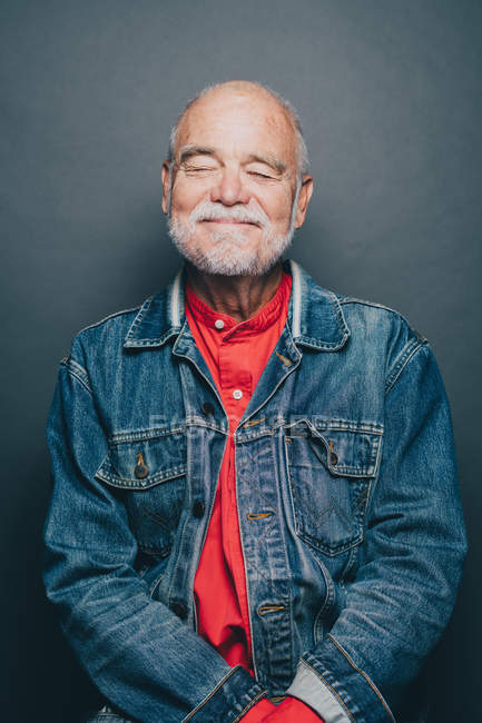 Smiling senior man with eyes closed standing against gray background — Stock Photo