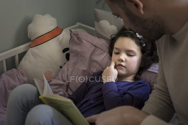 Father telling story while reading book to daughter on bed at home — Stock Photo