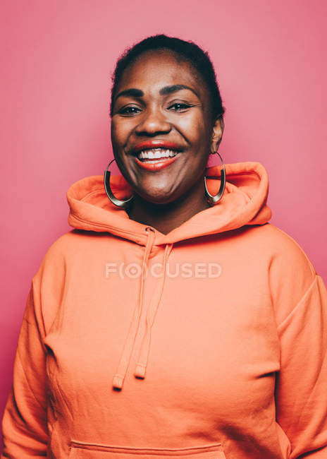 Portrait of smiling mid adult woman wearing orange hooded jacket over pink background — Stock Photo