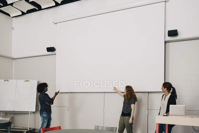 Confident multi-ethnic technicians giving presentation over blank projection screen at creative office — стоковое фото