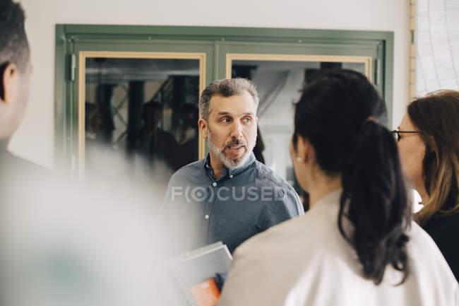 Uomo d'affari che discute con imprenditori multietnici alla conferenza — Foto stock