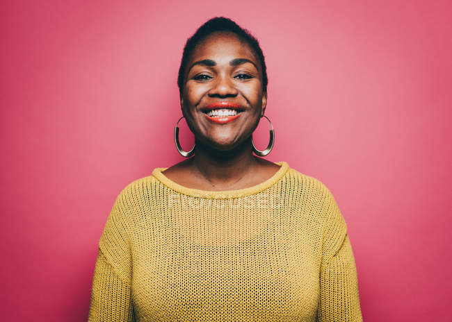 Portrait of smiling mid adult woman against pink background — Stock Photo