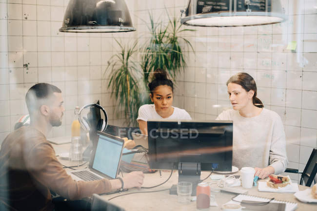 Young multi-ethnic computer programmers discussing at creative office seen through window — Stock Photo