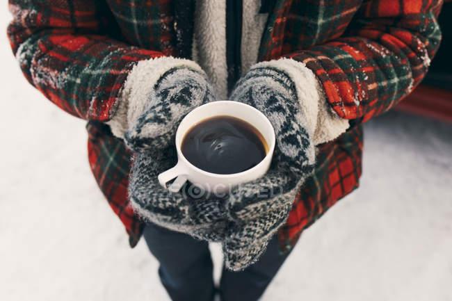 Середина человека, держащего чашку кофе, стоя на снегу — стоковое фото