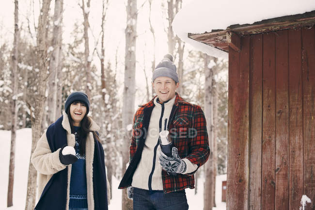 Portrait of happy friends holding snowball while standing by log cabin during winter — Stock Photo