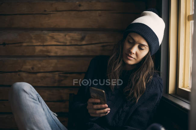 Woman using mobile phone while sitting in log cabin — Stock Photo