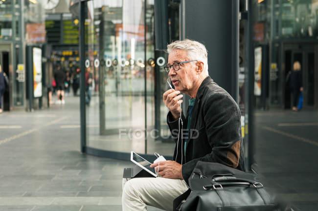Sénior comutador do sexo masculino falando através de fones de ouvido enquanto sentado por sacos na estação ferroviária — Fotografia de Stock