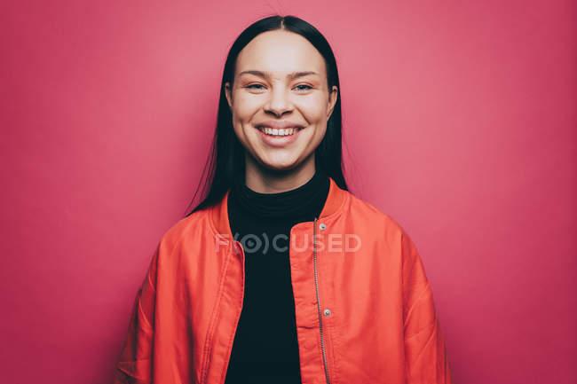 Портрет усміхається жінка, носіння помаранчевий куртка над рожевий фон — стокове фото