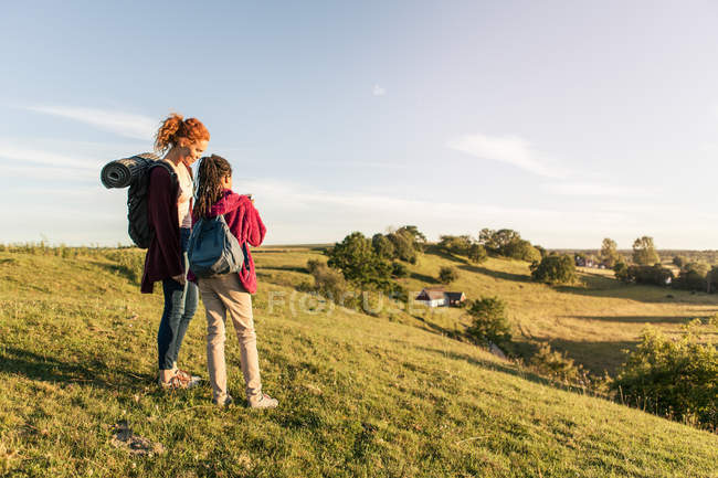 Mutter und Tochter mit Rucksäcken stehen bei Sonnenuntergang auf einem Hügel gegen den Himmel — Stockfoto