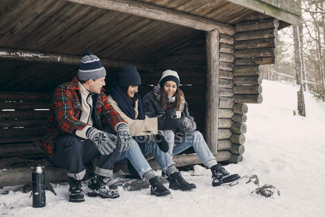 Friends sharing drink while sitting at log cabin during winter — Stock Photo