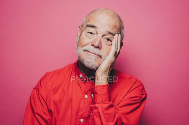 Retrato de entediado homem sênior com a cabeça na mão contra o fundo rosa — Fotografia de Stock