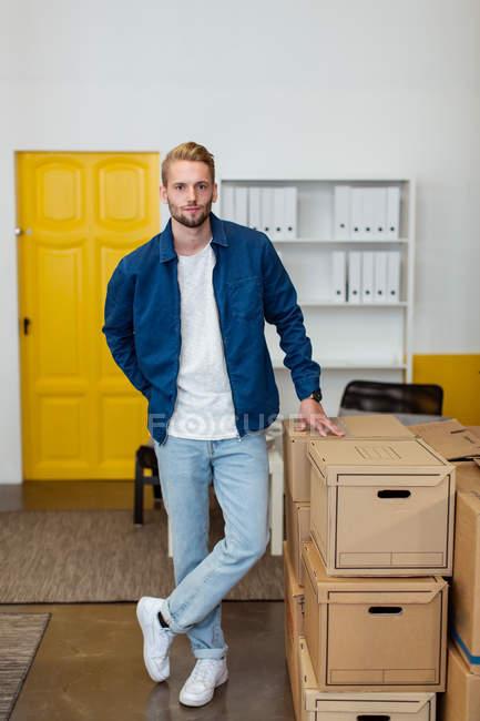 Portrait de jeune homme d'affaires confiant debout près des boîtes en carton empilent au bureau créatif — Photo de stock