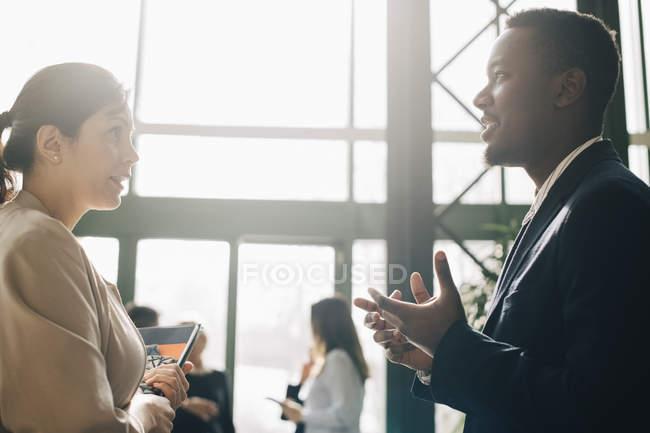 Homem de negócios que compartilha de idéias com colega fêmea na reunião no escritório — Fotografia de Stock