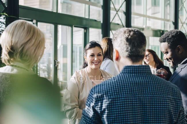 Empresária sorridente conversando com colegas em reunião no escritório — Fotografia de Stock