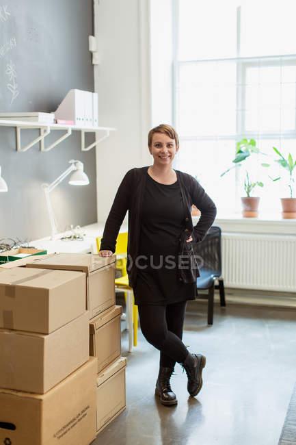 Portrait de femme d'affaires souriante debout près des boîtes en carton empilés contre la fenêtre au bureau créatif — Photo de stock