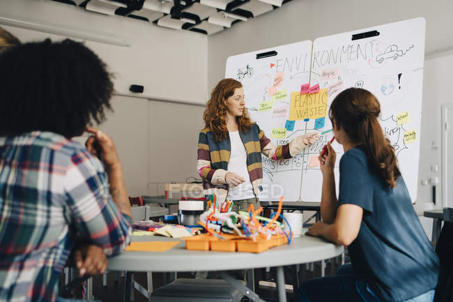 Confident businesswoman explaining plastic waste management plan to technicians over whiteboard at creative office — Stockfoto